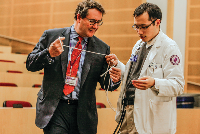 Seeing is Believing: Dr. Rosenkranz attired for his magic act working with a student.