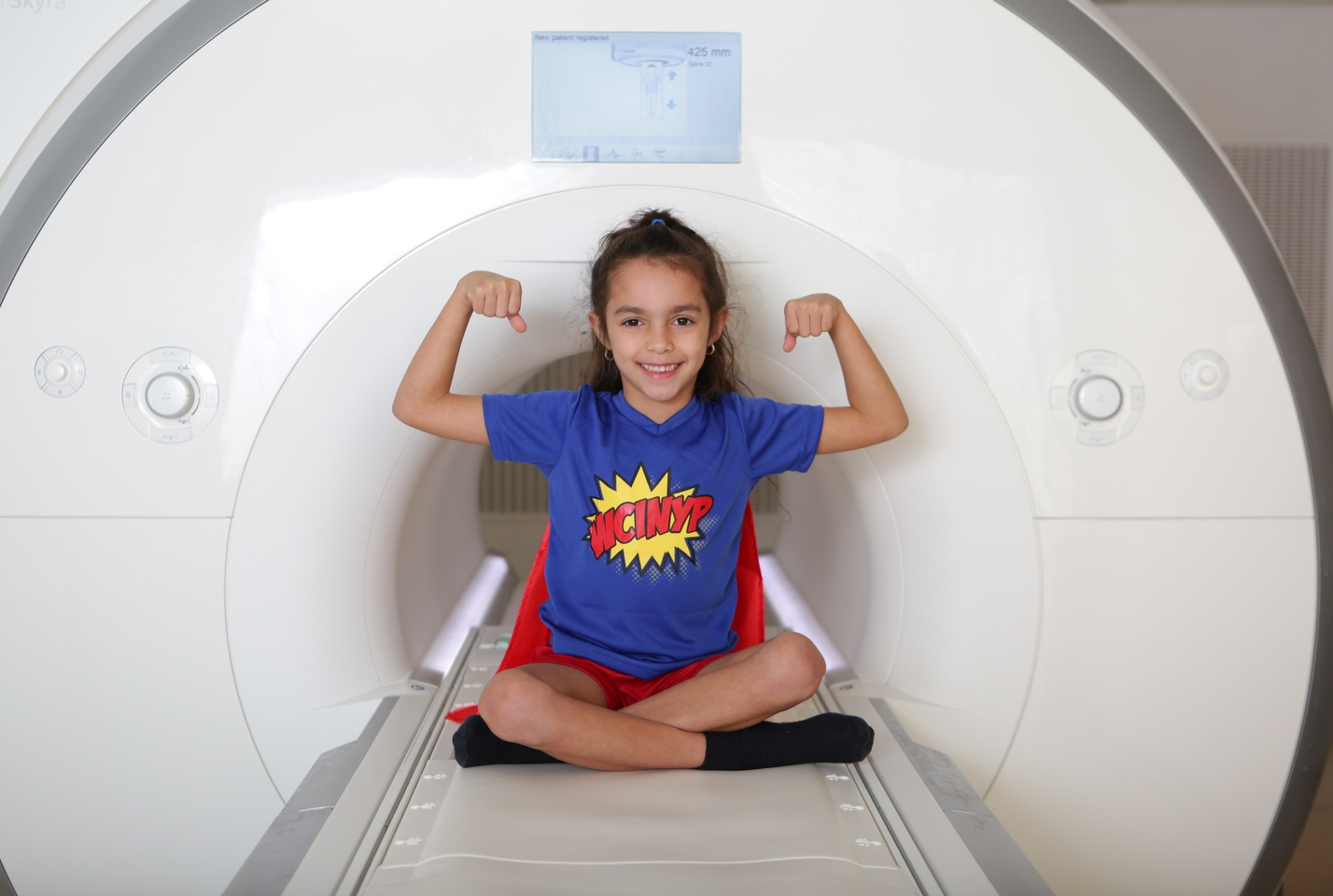 A young girl poses in an MRI machine
