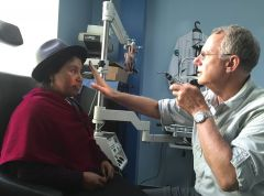 A doctor giving an eye exam to a patient